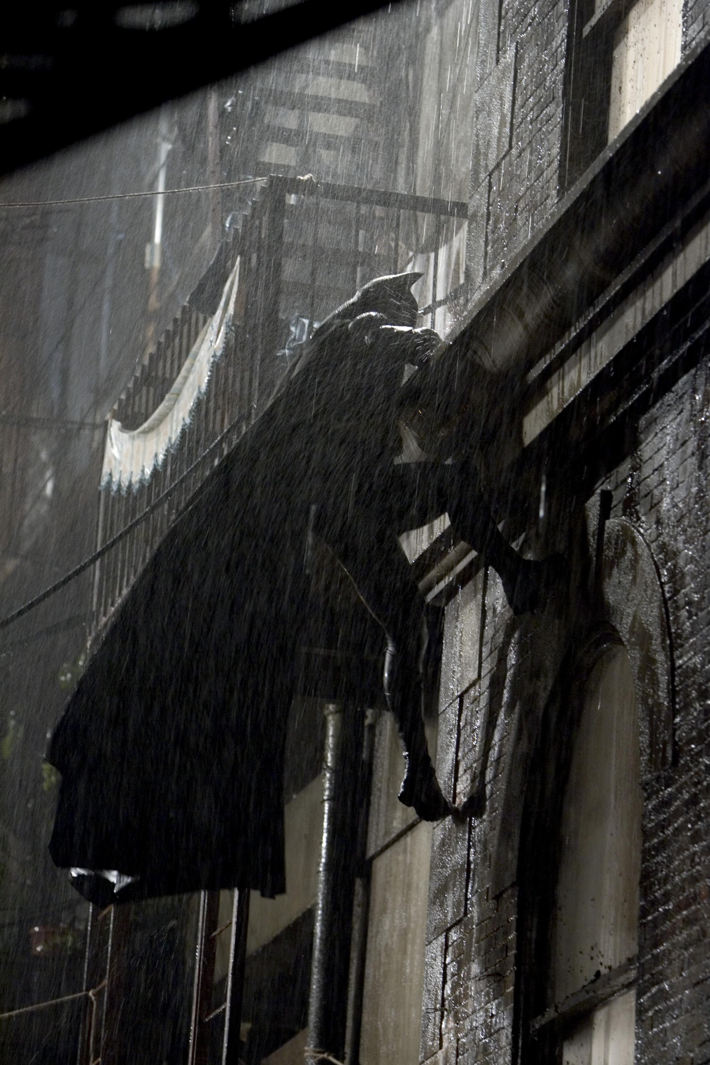 Batman climbs a rooftop