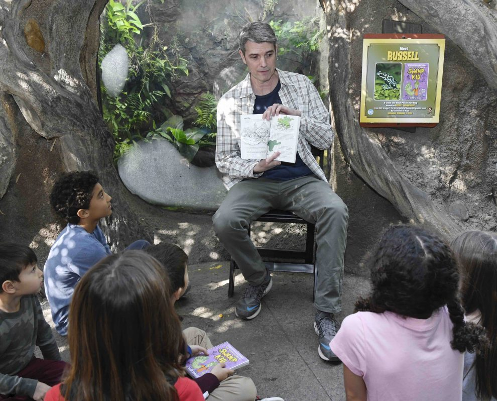 Scroggs reading at the frog exhibit